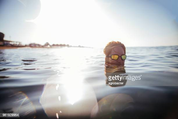 women swimming in sea against sky - sea swimming stock photos and pictures