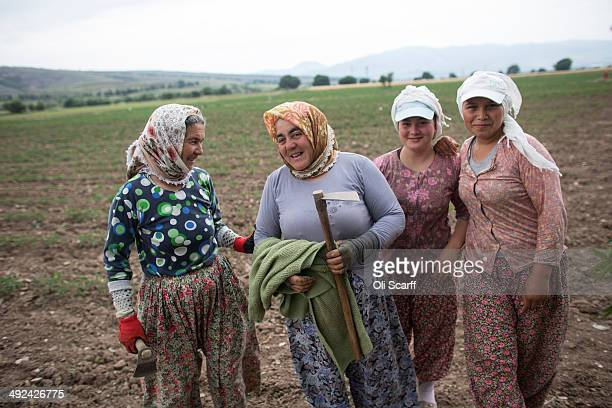 Women take a break from planting crops by hand in a field near the town of Soma, whose economy relies heavily on the mining industry, on May 20, 2014...