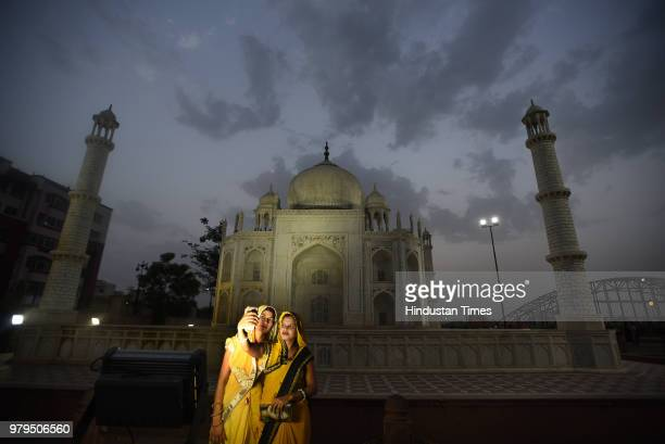 Women take a picture in front of the Taj Mahal but instead of Agra this one is in Seven Wonders Park situated on the banks of Kishore Sagar Lake of...