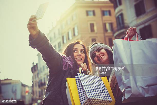 women take a selfie during christmas shopping in rome - black friday stock pictures, royalty-free photos & images