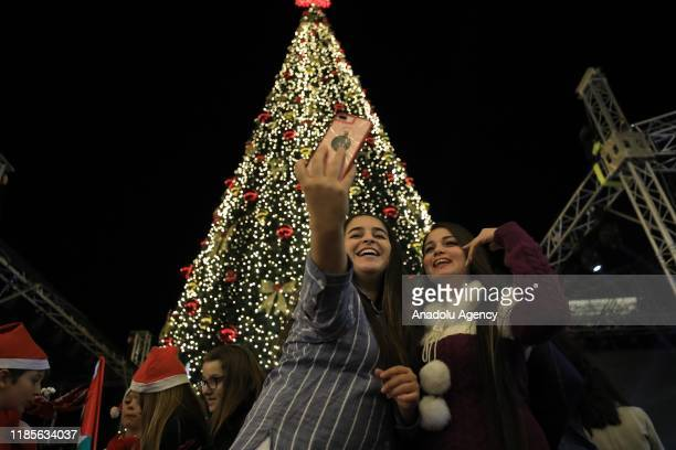 Women take a selfie in front of a Christmas tree installed at the Manger Square near the Church of the Nativity revered as the site of Jesus Christ's...