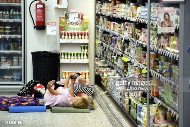 TOPSHOT Women take a selfie next to cooling shelves in a local grocery store that invites customers for a sleepover to cool off as the heatwave in...