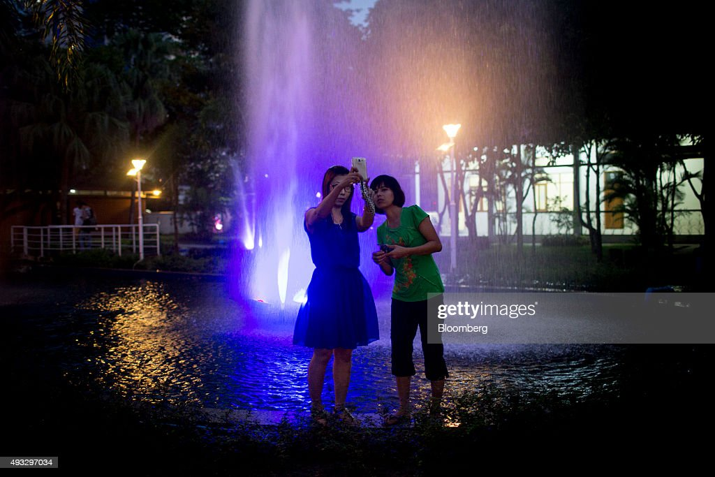Women take a selfie photograph with a smartphone in front of an illuminated water fountain in Maha Bandoola Garden at night in Yangon, Myanmar, on Wednesday, Oct. 14, 2015. Myanmar's government signed a cease-fire agreement with half of the nation's armed ethnic groups, a partial victory for President Thein Sein less than a month before an historic national election. Photographer: Brent Lewin/Bloomberg via Getty Images