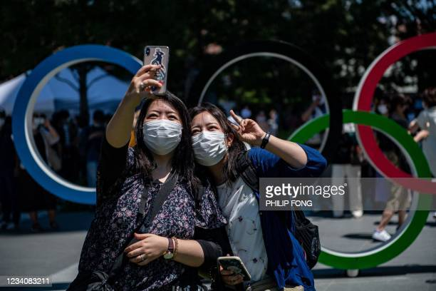 Women take a selfie picture in front of the Olympic Rings near the Olympic Stadium in Tokyo, on July 21, 2021 ahead of the Tokyo 2020 Olympic Games.