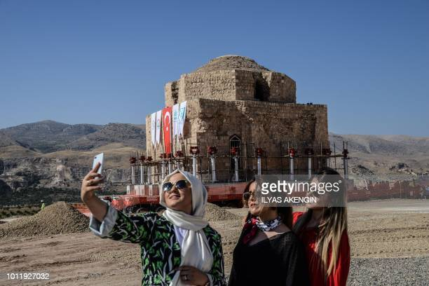 Women take a selfie picture with their mobile phone as the Artuklu Hamam a centuriesold bath house weighing 1600 tonnes is loaded onto a wheeled...