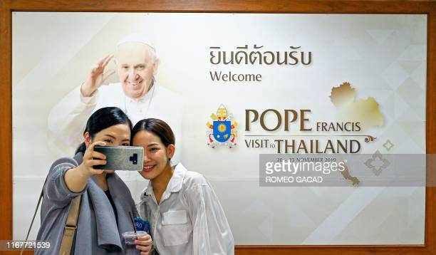 Women take a selfie with a poster about Pope Francis' upcoming trip to Thailand in Bangkok on September 13 2019 Pope Francis will travel to Thailand...