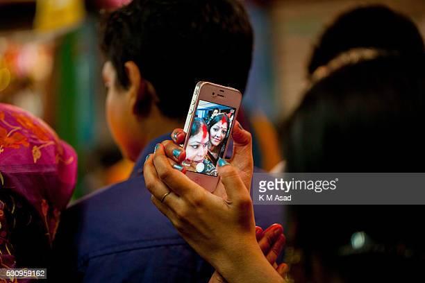 Women take a selfie with mobile phone when they make ritual for Hindu god to Bipadtarini Devi in Dhaka Bangladesh July 25 2015 During the ritual of...