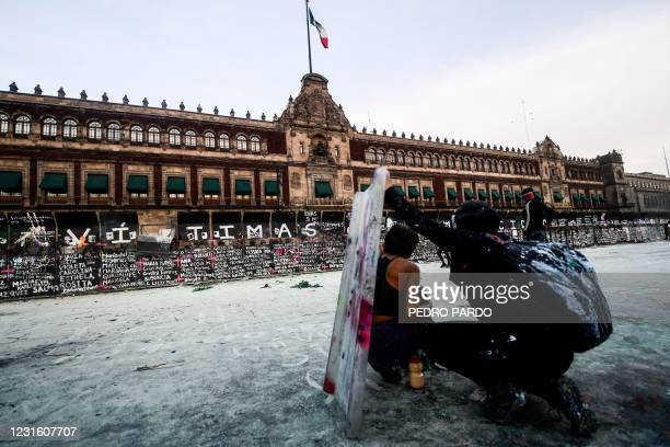 Women take cover as they clash with the police, behind a fence in front of the National Palace, as they protest during a demonstration to commemorate...