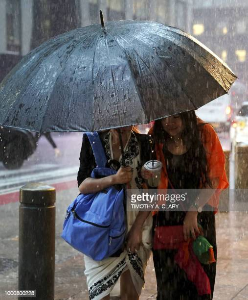Women take cover from the rain in Midtown New York on July 17 2018 as a sudden storm hit the area with flash food warning in the tristate area
