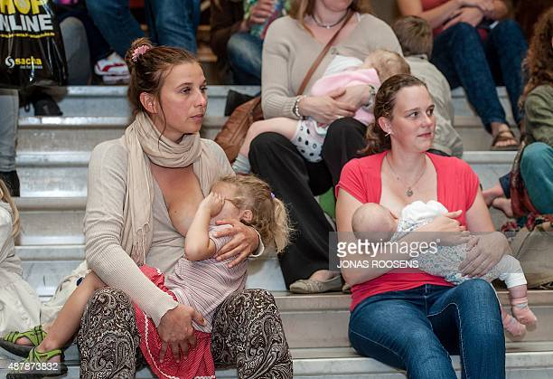 Women take part in a breastfeeding flashmob to campaign for mothers' rights to breastfeed their babies in public in Antwerp on September 12 2015 OUT...