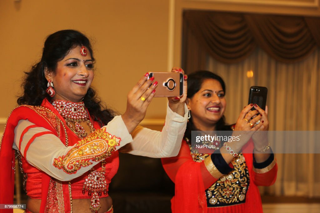 Women take photos during a fashion show held as part of the Diwali Gala Celebration in Mississauga Ontario Canada on 25 November 2017 This luxurious..