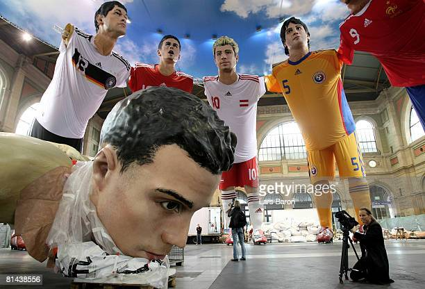 A women take pictures of a giant three dimensional display of Robin von Persie of Netherlands being stored in front of three dimensional displays of...