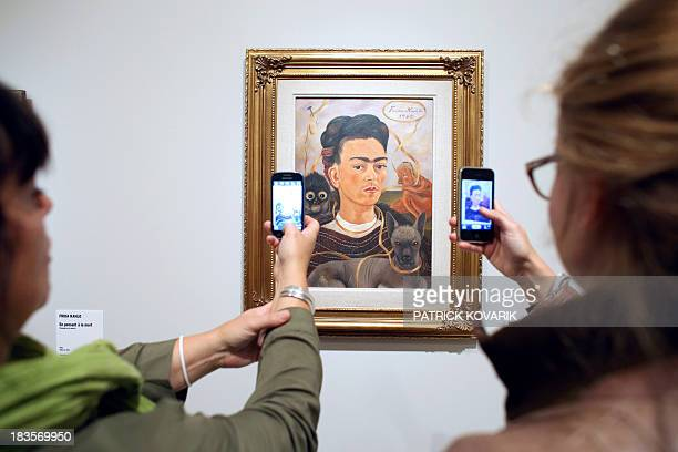 Women take pictures of an autoportrait by Mexican painter Frida Kahlo during the exhibition 'Frida Kahlo / Diego Rivera Art in fusion' at the Musée...