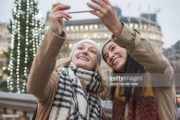 Women take Selfie with portable information device at urban square.