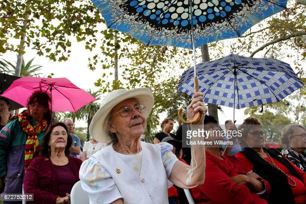 Women take shelter under umbrellas during the ANZAC service at Redfern Park on April 25 2017 in Sydney Australia The annual ANZAC coloured diggers...