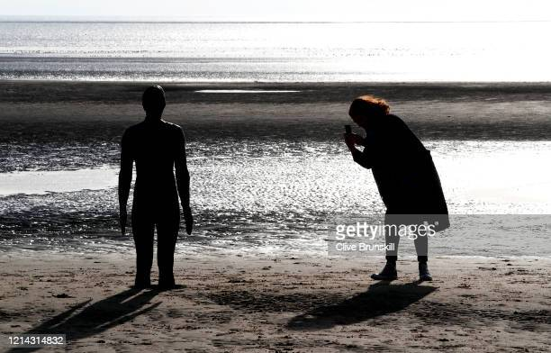 A women takes a photograph of one of the 'Iron Men' that form part of Antony Gormley's 'Another Place' sculpture during a quiet walk on Crosby beach...