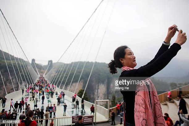 Women takes a picture side of glass-floor suspension bridge in Zhangjiajie in south China's Hunan province on October 14, 2016 in Zhangjiajie, China....