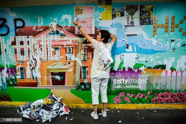 TOPSHOT A women takes down posters put up by antigoverment protesters as part of a Lennon Walls in the Mong kok district of Hong Kong on September 21...