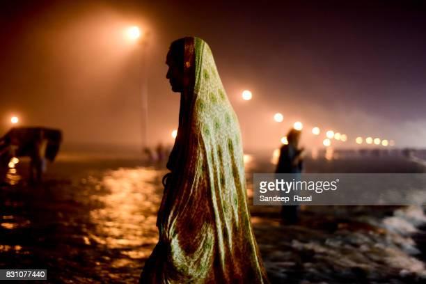 a women taking a holi dip  during ganga sagar fair - ganga sagar stock photos and pictures