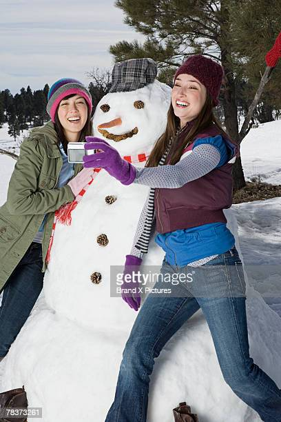 Women taking a picture with snowman