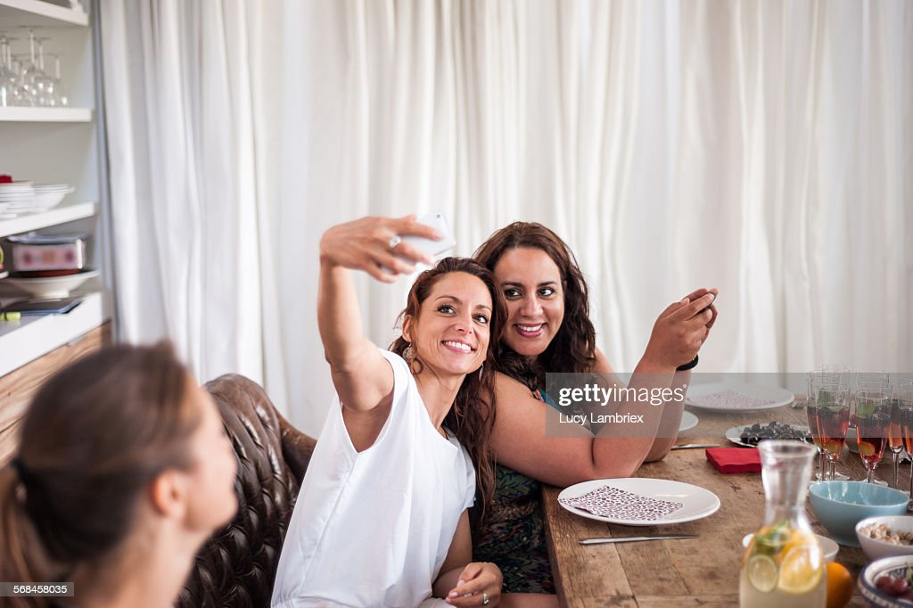 Women taking a selfie at dinner table. : Stock Photo