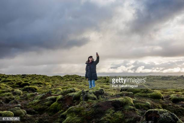 a women taking a selfie on lava moss field in iceland - territorio selvaggio foto e immagini stock