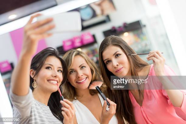 Women taking a selfie while applying makeup