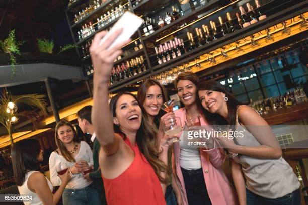 women taking a selfie while having drinks at the bar - cocktail party stock pictures, royalty-free photos & images
