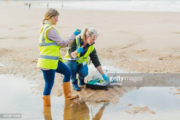donne che prendono un campione d'acqua - biologo foto e immagini stock