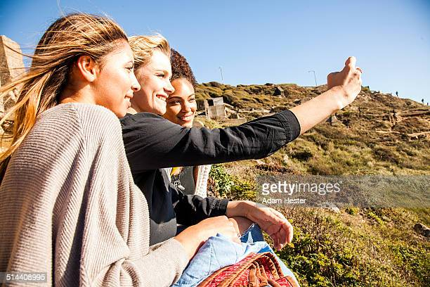 Women taking cell phone picture together on rural hillside