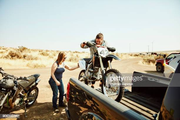 Women taking dirt bike out of bed of truck before desert ride