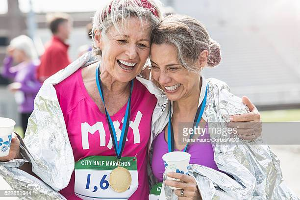 women taking part in road race having medals and celebrating winning - ハーフマラソン ストックフォトと画像