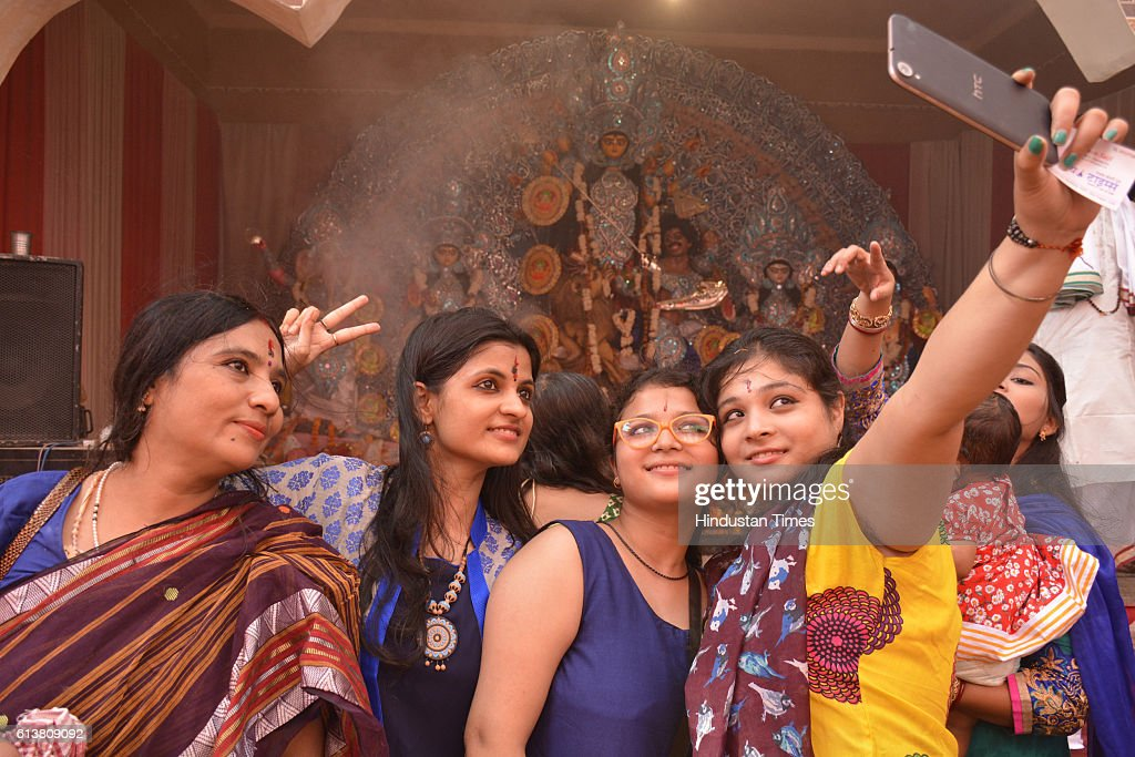 Women taking selfie with the idol of Goddess Durga at Durga Puja pandal on October 10, 2016 in Ghaziabad, India.