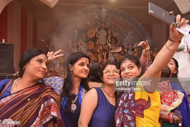 Women taking selfie with the idol of Goddess Durga at Durga Puja pandal on October 10 2016 in Ghaziabad India