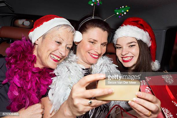 Women taking Selfies wearing Christmas hats in car