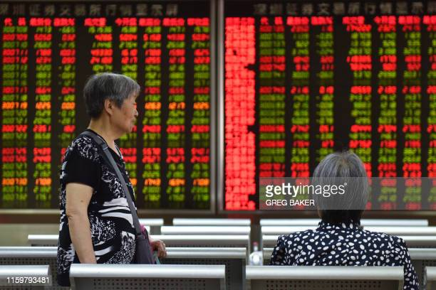 Women talk in front of a screen showing stock prices at a securities company in Beijing on August 5 2019 Asian markets plummeted on August 5 as the...