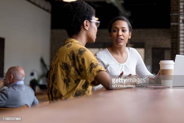 women talk while having coffee together - serious stock pictures, royalty-free photos & images