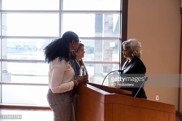 women talk with female political candidate - town hall meeting stock pictures, royalty-free photos & images