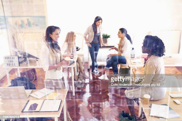 Women talking behind glass wall in office