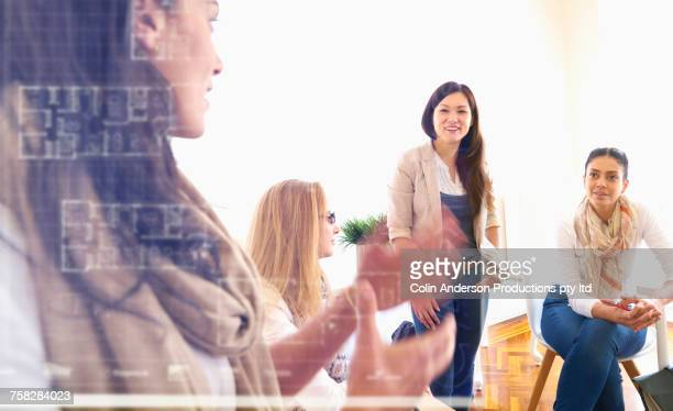 Women talking behind the glass wall in office