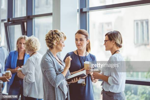 women talking during coffee break at convention center - talking stock pictures, royalty-free photos & images