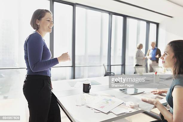 women talking in design office meeting room - older women in short skirts stock pictures, royalty-free photos & images