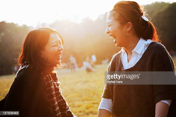 women talking in the park - two people ストックフォトと画像