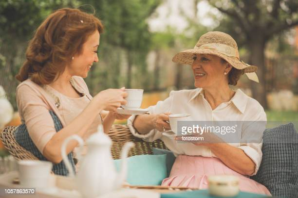 women talking over a cup of tea - tea party stock pictures, royalty-free photos & images