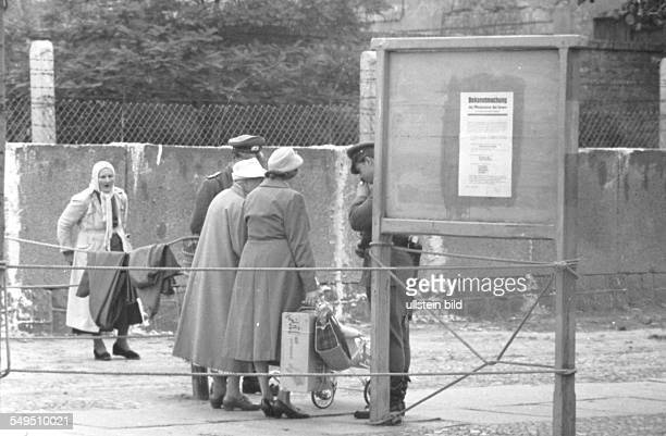 Women talking to East German border guards at the fenced off sector border at Bernauer Strasse