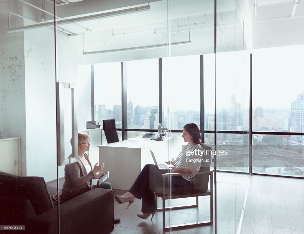Women talking together in business office : Stock-Foto