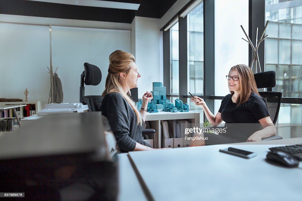 Women talking together in design office : Stock Photo