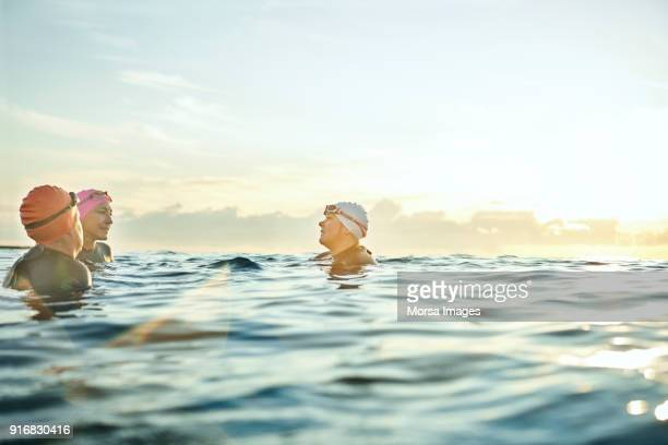 women talking while swimming in sea during sunset - active seniors stock pictures, royalty-free photos & images