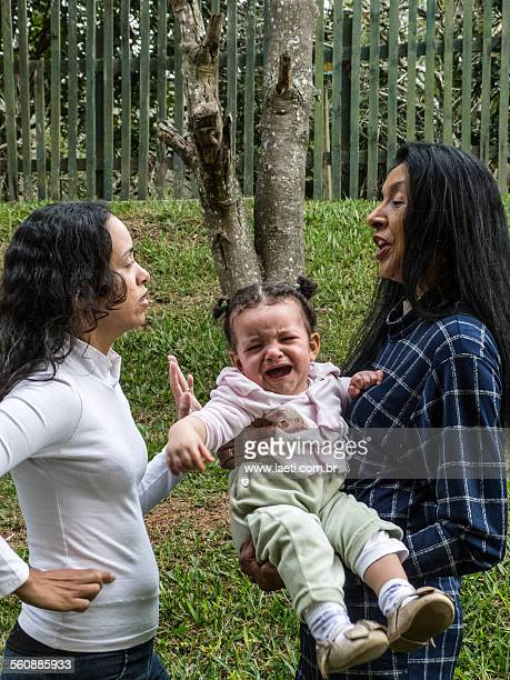 Women talking with a child crying.