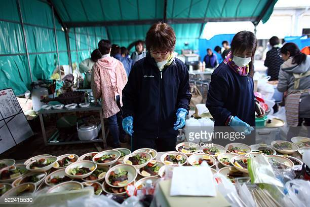 Women temporarily displaced by the earthquake prepare food for neighbouring families as supplies are delivered by the Japan Self-Defense Force, on...